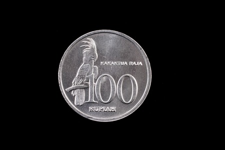 An extreme close up of an Indonesian 100 rupiah coin on a solid black background