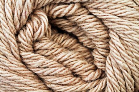 A super close up image of tan yarn