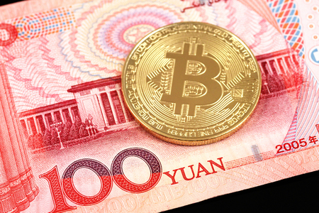 A close up image of a 100 yuan note with a bitcoin