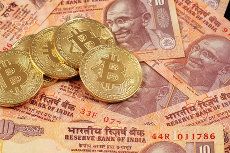 A close up image of bitcoins with Indian rupee notes Foto de archivo