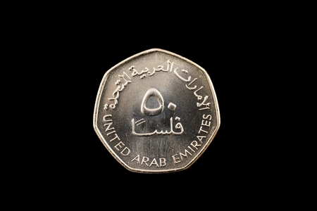 A macro image of a United Arab Emirates 50 fils coin isolated on a black background