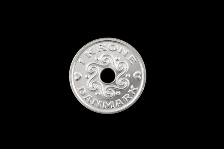 A close up image of a silver 1 krone coin isolated on a black background 版權商用圖片