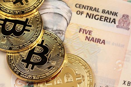 A close up image of Nigerian 5 Naira bank notes with gold bitcoins Stock Photo