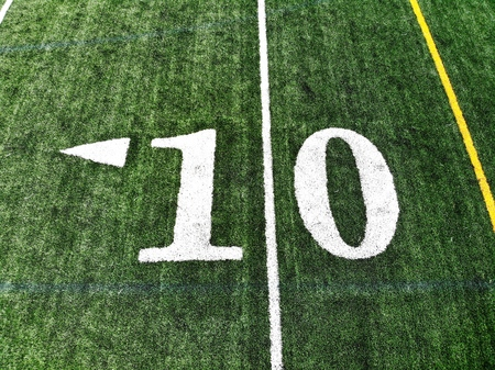 10 yard chalk mark on an green American football field taken from an aerial drone Stock Photo
