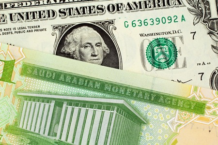 A close image of a green one Saudi Riyal note with an American one dollar bill