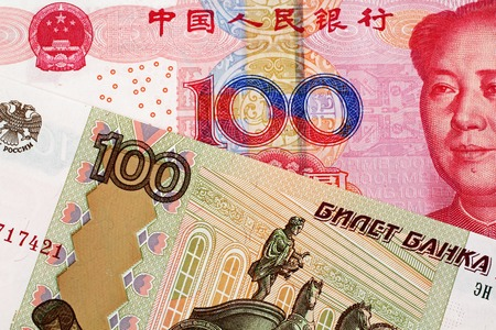 A close up image of a 100 Chinese yuan bank note with a 100 Russian ruble bank note