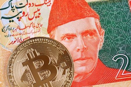 A macro image of a 20 Pakistani rupee note with a gold bitcoin Фото со стока