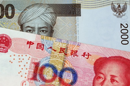 A close up image of a 100 Chinese yuan bank note with a 2000 Indonesian Rupiah bank note