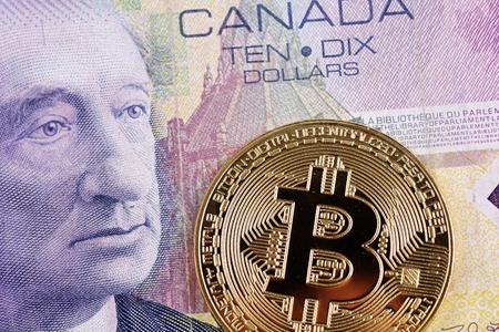 A close up image of a Canadian ten dollar bill with a golden bitcoin Фото со стока