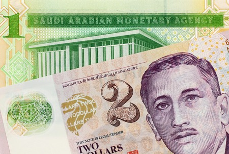 A close up image of a one Saudi Riyal note with a two Singapore dollar bank note Archivio Fotografico