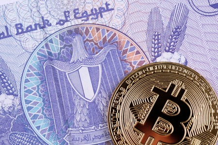 A close up image of a golden bitcoin with an Egyptian twenty five piastres bill