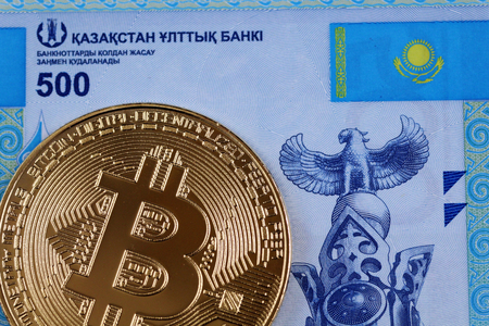 A close up image of a blue five hundred Kazakhstani tenge bill with a golden bitcoin