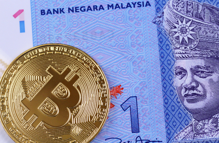 A blue one Malaysian ringgit banknote with a golden bitcoin