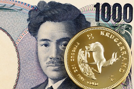 A macro image of a Japanese 1000 yen bill with a gold Krugerrand bullion coin
