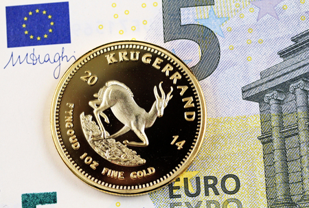A close up image of a five Euro bank note with a gold Krugerrand one ounce coin