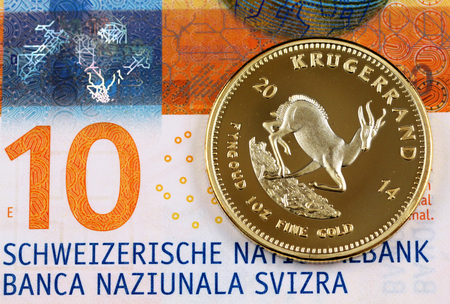 A macro image of a ten Swiss Franc bank note with a one ounce Krugerrand coin