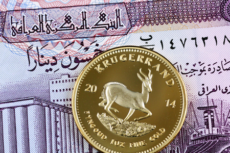 Close up image of an Iraqi 50 dinar bank note with a golden South African krugerrand coin Stock Photo
