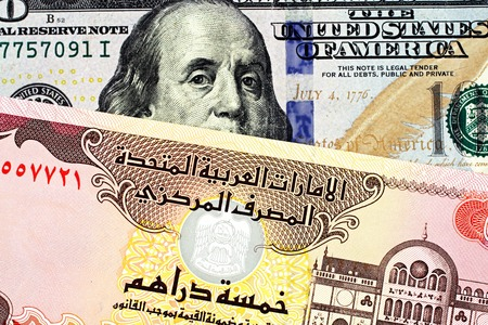 A close up image of a blue American one hundred dollar bill with a 5 dirham United Arab Emirates bank note Stock Photo