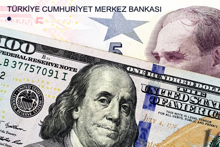 A close up image of a blue American one hundred dollar bill with a five Turkish lira bill