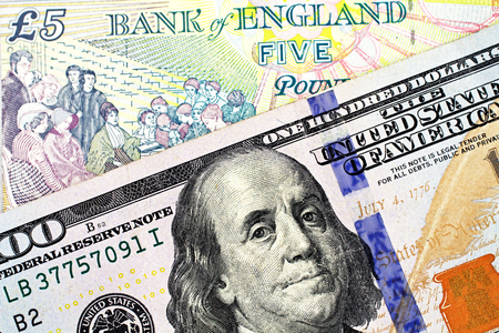 A close up image of a five pound note from England with a blue, American one hundred note Archivio Fotografico