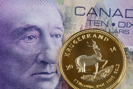 A close up image of a Canadian ten dollar bill with a golden South African krugerrand