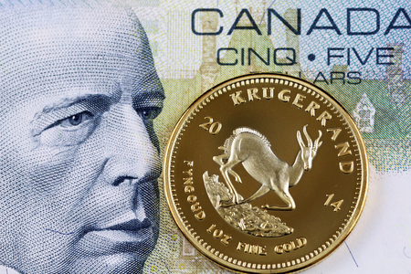 A close up image of a Canadian five dollar bill with a golden South African krugerrand Stock Photo