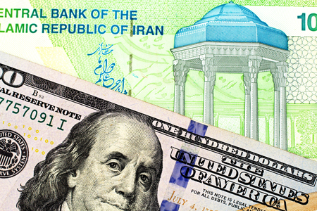 An American one hundred dollar bill in macro with an Iranian ten thousand rial note