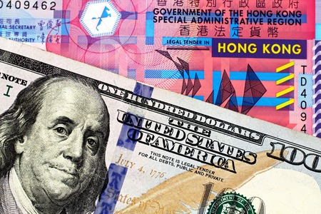 A macro image of a ten Hong Kong dollar bill with a blue American one hundred dollar bill