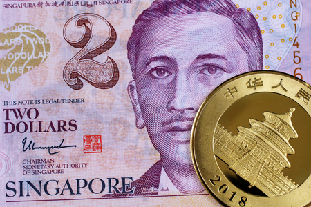 A macro image of a purple two Singapore dollar bank note with a Chinese gold panda one ounce coin. Stock Photo