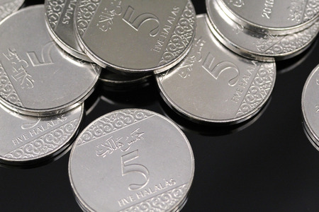 A pile of shiny new five halala coins in macro on a reflective black background Stock Photo