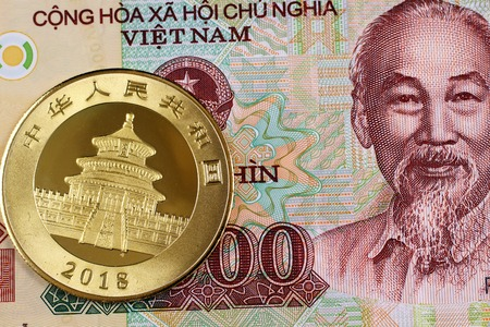 A colorful ten thousand Vietnamese dong note with a Chinese one ounce gold coin