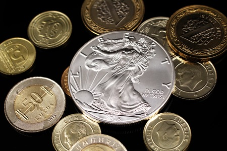 A macro image of an assortment of Turkish coins and a silver American one ounce coin on a reflective black background