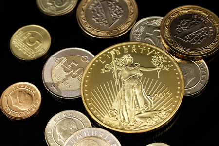 A macro image of an assortment of Turkish coins and a gold American one ounce coin on a reflective black background Stock Photo