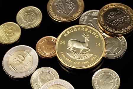 A macro image of an assortment of Euro coins and a gold South African one ounce Krugerrand coin on a reflective black background