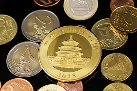 A macro image of an assortment of Euro coins and a gold Chinese one ounce coin on a reflective black background Stock Photo