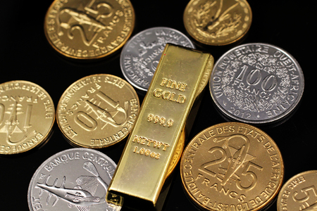A macro image of an assortment of West African Franc coins and a gold one ounce ingot on a reflective black background