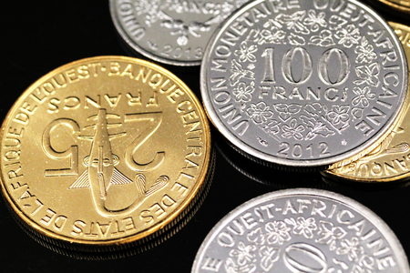 A macro image of an assortment of West African Franc coins on a reflective black background
