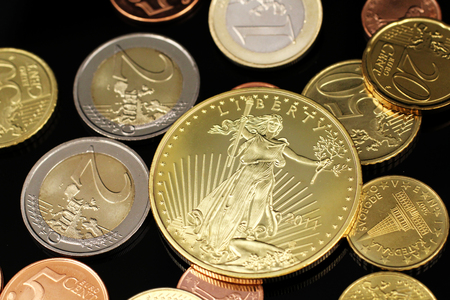 A macro image of an assortment of Euro coins and a gold American one ounce coin on a reflective black background Stock Photo