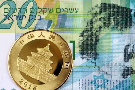 A macro image of a green twenty new Israeli shekel banknote with a shiny, new Chinese gold panda coin