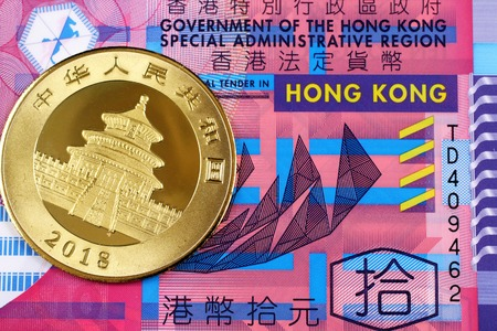 A macro image of a purple and blue ten Hong Kong bank note with a shiny, new Chinese gold panda coin