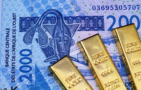A close up image of three gold bars with a two thousand West African Franc bank note in macro Stock Photo