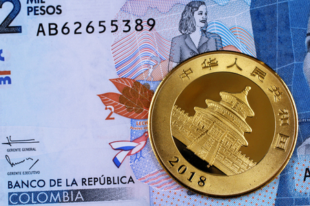 A Chinese one ounce gold coin with a Colombian two thousand peso bill shot in macro