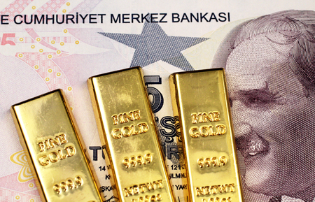 A purple five Turkish lira bank note in macro with three small gold bars Stock Photo