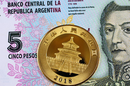 Three one ounce gold bars with a five peso bank note from Argentinia shot in macro