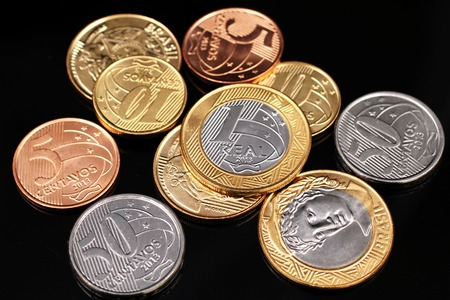 A macro image of miscellaneous Brazilian coins on a black reflective background close up Zdjęcie Seryjne
