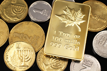 A macro image of miscellaneous coins from Israel with a Canadian one ounce gold ingot on a reflective black background Stock Photo