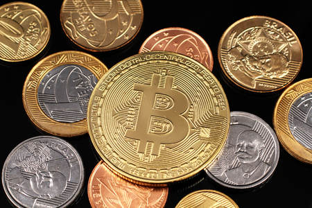 A macro image of miscellaneous Brazilian coins with a gold physical Bitcoin on a black reflective background close up