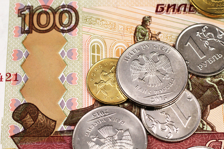 A close up image of Russian coins on a one hundred Russian ruble bank note Stock Photo