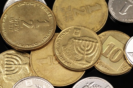 A macro image of miscellaneous coins from Israel on a reflective black background
