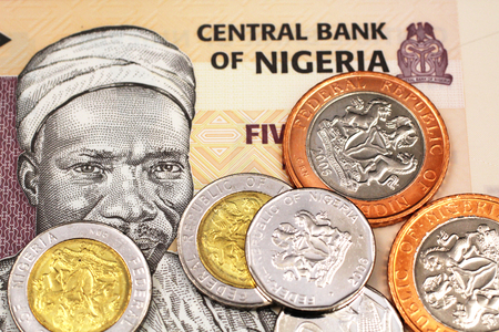 A macro image of miscellaneous Nigerain coins on a five Naira bank note from Nigeria Stock Photo